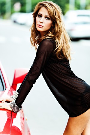 pretty woman in black transparent dress rest upon red car, outdoor shot Stock Photo - 8005299