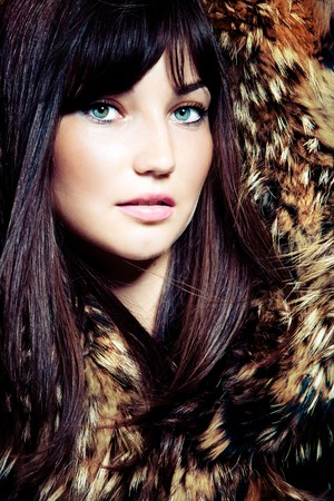 young blue eyes woman portrait with fur, studio shot photo