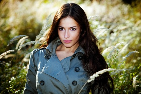 topcoat: young woman in topcoat walking accros the autumn meadow Stock Photo