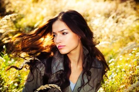 autmn: young woman portrait in autumn field, wind in hair
