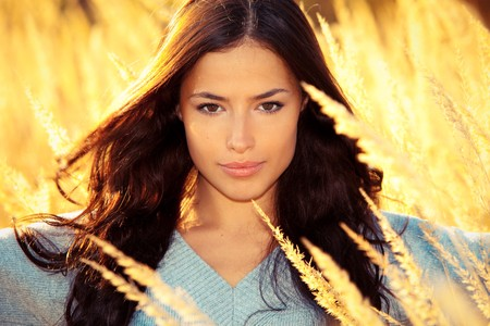 young brunette woman  portrait at sunny yellow autumn field photo