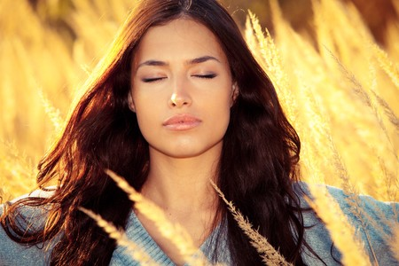 young woman portrait with eyes closed enjoy in autumn sun on yellow field photo