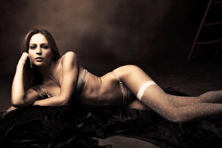 sensual brunette woman in underwear lie on floor posing, studio shot photo