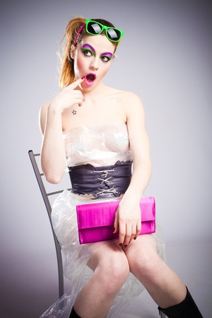 young woman in plastic dress and heavy make up and wonderment expression studio shot photo