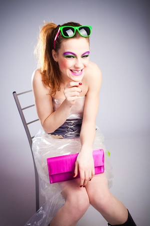 young woman in plastic dress and heavy make up with malicious smile studio shot photo
