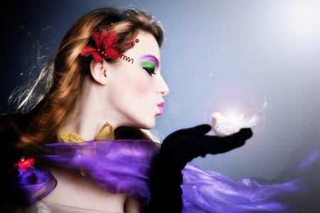 beautiful fairy sending a kiss to a little bird on her palm, profile,  studio shot Stock Photo - 8599729