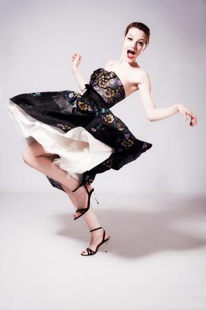happy young woman dancing in fancy dress, studio shot, full body shot photo