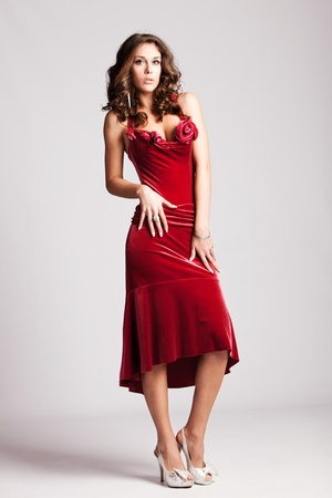 brunette woman in red elegant dress, full body shot, studio shot photo