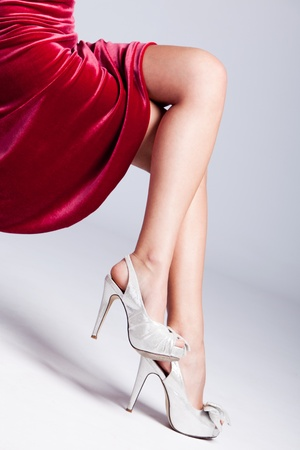 fancy dress: beautiful female long legs in elegant high heels shoes, studio shot, focus on shoes Stock Photo