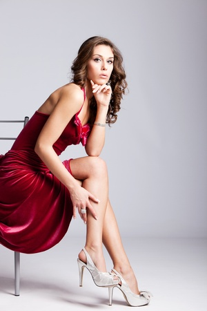 fashion shoes: young elegant woman in red dress sit on chair, studio shot