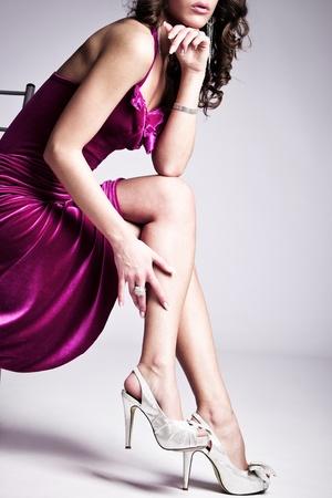 mujer con vestido elegante color púrpura y tacones altos sentarme en silla, studio disparo