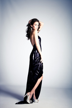 young brunette woman in long elegant dress, standing full body shot, studio shot photo
