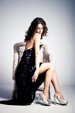 young woman in long elegant dress, sit in arm chair, full body shot, studio shot photo