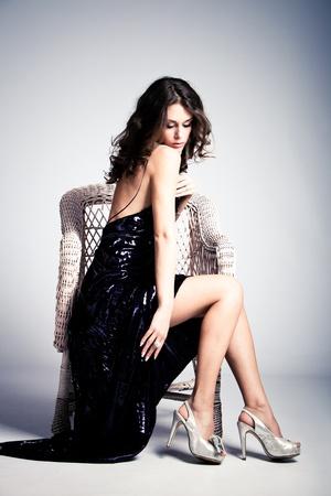 young woman in long elegant dress, sit in arm chair, full body shot, studio shot Stock Photo - 8684145