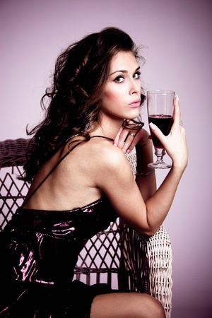young elegant woman sit in armchair holding a glass of red wine, studio shot photo