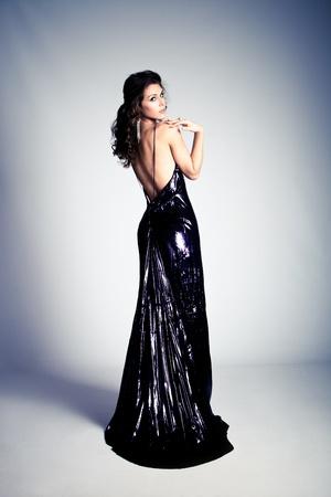 long shot: giovane donna stand in rosso vestito elegante, dal corpo posteriore, completo girato, studio shot
