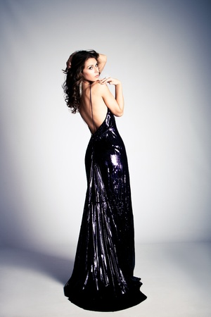 young brunette woman in long elegant dress, studio shot photo