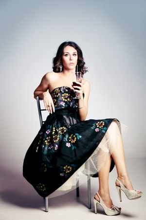 woman in elegant dress sit and hold a glass of red wine, studio shot photo