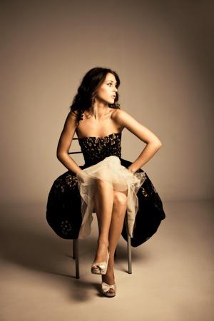 full body shot: disparo de todo el cuerpo de mujer joven en sit elegante vestido en silla, studio dispararon, Foto de archivo