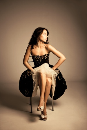 high fashion: young  woman in elegant dress sit on chair, studio shot, full body shot