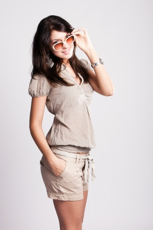 summer clothes: young brunette woman in summer clothes and sunglasses smiling, studio shot