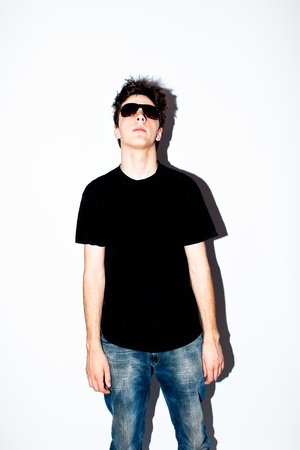 purposely: young man wearing sunglasses,  black t shirt and jeans agains white background, shot purposely with direct flash