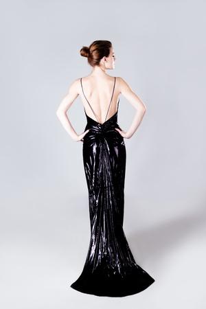 bollos: mujer joven en elegante cuerpo visten durante mucho tiempo, completa filmada, volver, disparo de studio Foto de archivo