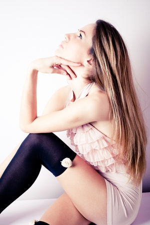 hosiery: young sensual blond woman in pink romantic shirt and black hosiery, sitting, profile, indoor shot Stock Photo