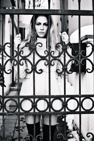 young woman with serious expression standing behind entrance gate, outdoor shot, winter day, grain added, bw photo