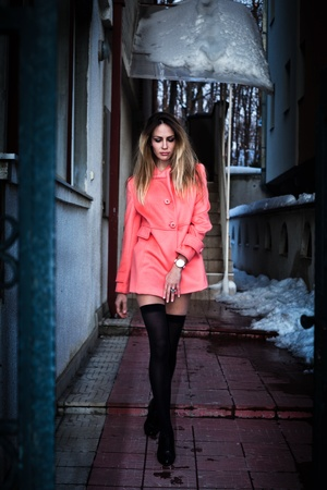 house coat: young woman in short pink coat and black stockings walking from house, winter dusk