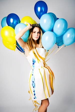 celebration people: young woman in beautiful elegant dress holding lot of balloons, studio shot