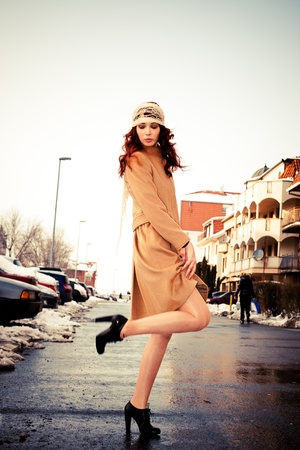 young woman wearing coat walking down the street, cold winter day photo