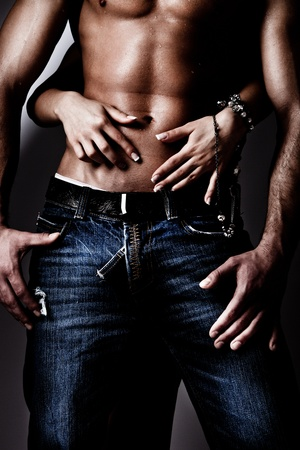 shirtless wet muscular man in jeans and woman hands, studio shot Stock Photo - 9103497