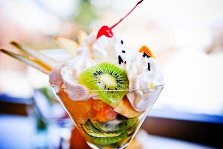 fruit salad with cream served in glass in restaurant, ambient light photo