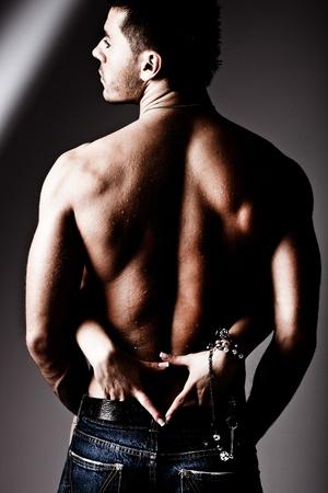 sensuel: biceps humide musculaire man en jeans et des mains de femme, studio abattu Banque d'images