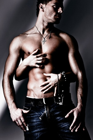 shirtless wet muscular man in jeans and woman hands, studio shot Stock Photo - 9103394