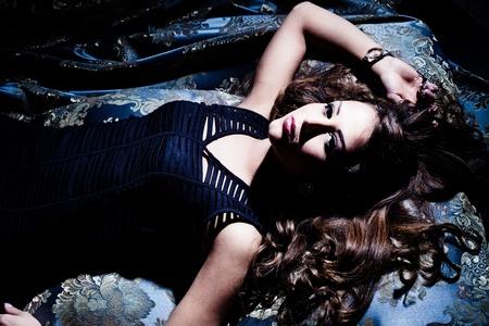 boudoir: sensual young brunette woman lie down,  studio shot Stock Photo