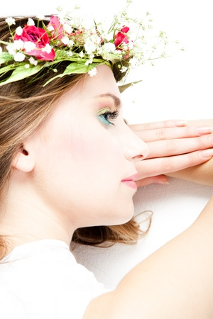 young blond woman beauty portrait with wreath of flowers, studio shot photo