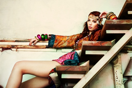 vogue: young woman in colorfull summer clothes sit on stairs indoor shot Stock Photo