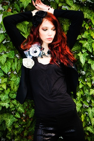 red hair fashion woman in black with fashion accessories agains wall with green rambler plant Stock Photo - 9292267