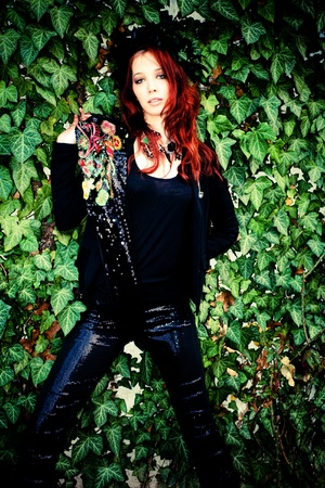 rambler: red hair fashion woman in black with fashion accessories against wall with green rambler plant Stock Photo