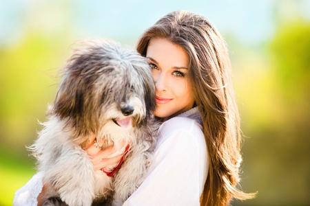 mujer con perro: mujer joven con retrato de d�a al aire libre de perro