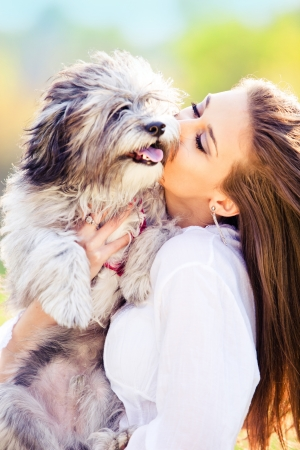 young woman kissing her litlle dog, outdoor shot photo