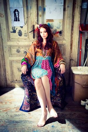 barrettes: donna in abiti colorati sedersi di fronte porta in studio di lavoro di artista Archivio Fotografico