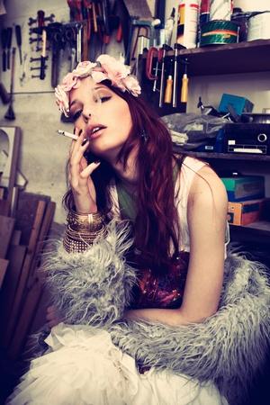 headband: fashion girl in artist studio smoking cigarette Stock Photo