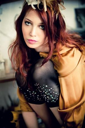 cintillos: mujer de pelo rojo en vestido dorado y cintillo con tiro interior de adorno de oro