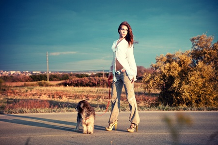 young woman with her dog stand on the road, summer day photo