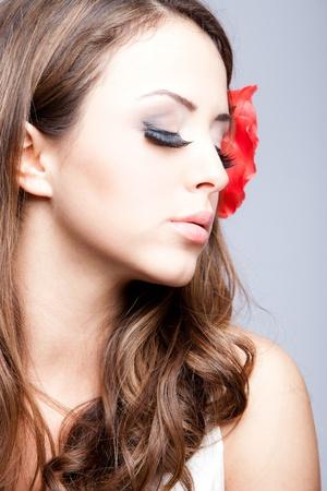 young brunette woman beauty portrait, flower in hair, profile, studio shot Stock Photo - 9413747