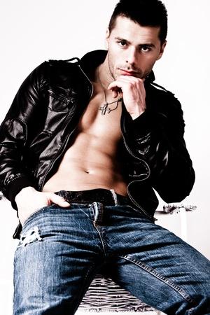 hombre fuerte: jóvenes sin camisa guapo en la chaqueta de cuero y pantalones vaqueros, studio disparo