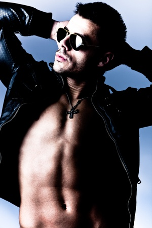 macho: handsome young shirtless man in leather jacket and sunglasses, studio shot Stock Photo